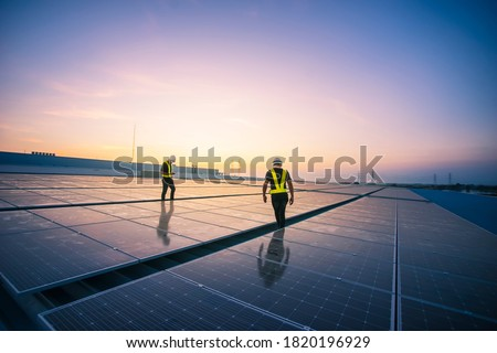 Technology solar cell, Engineer service check installation solar cell on the roof of factory on the morning. Silhouette technician inspection and repair solar cell on the roof of factory. Royalty-Free Stock Photo #1820196929