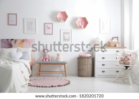 Modern teenager's room interior with comfortable bed and beautiful pictures