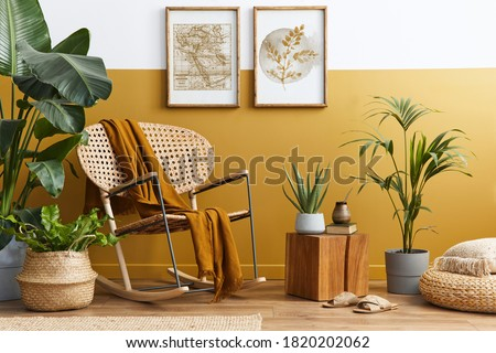 Stylish composition of living room interior with design rattan armchair, two mock up poster frames, plants, cube, palid and personal accessories in honey yellow home decor. Template. Royalty-Free Stock Photo #1820202062