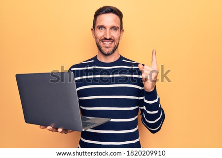 Young handsome man working using laptop standing over isolated yellow background smiling happy pointing with hand and finger to the side