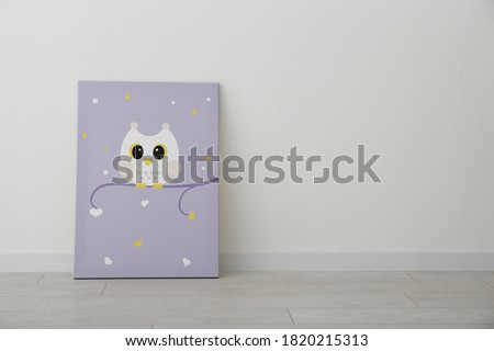 Adorable picture of owl on floor near white wall, space for text. Children's room interior element