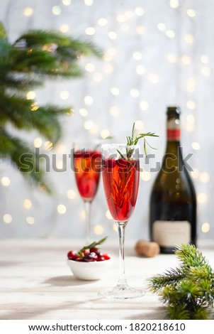 Mimosa festive drink for Christmas - champagne red cocktail Mimosa with cranberry for Christmas party, copy space and fir tree branches vertical photo #1820218610