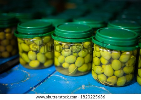 Pickled olives in glass jars at store warehouse. High quality photo