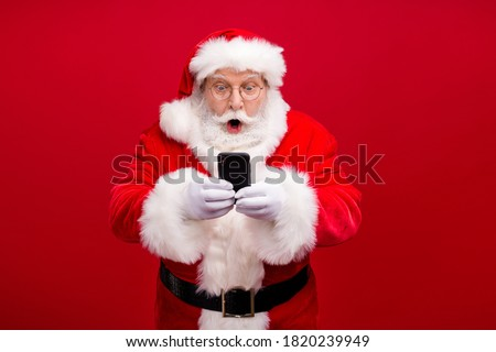 Portrait of his he nice attractive handsome amazed stunned Santa using gadget 5g fast speed blog blogger browsing multimedia isolated over bright vivid shine vibrant red color background