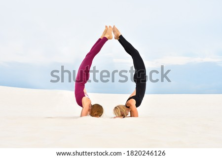 Two beautiful young women doing stand on the forearms together on the beach Royalty-Free Stock Photo #1820246126