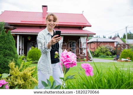 Young beautiful woman florist take photo of blooming peonies flowers in outdoor garden. Female gardener takes pictures of garden plants on phone, growing flowers on backyard, lifestyle, gardening