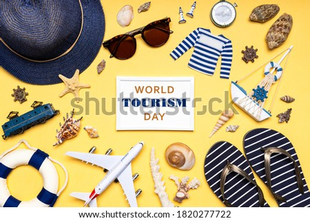Happy world tourism day! Touristic clothes, hat, flip-flops, sunglasses and decorative items on light pastel background. Flat lay, top view. White photo frame with text WORLD TOURISM DAY