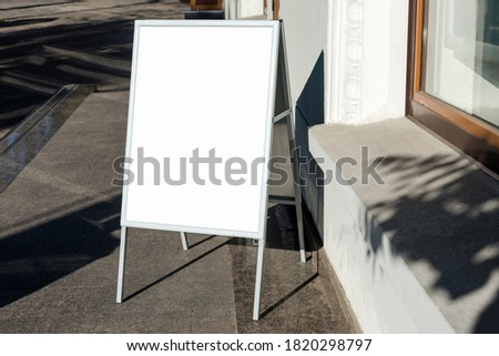 Signboard on the street. Angled empty menu board stand. Restaurant sidewalk white sign board. Freestanding A-frame advertising board near outdoor cafe. Selective focus