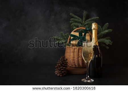 Christmas holiday hamper with glass of sparkling wine and gift on black background. Xmas greeting card.