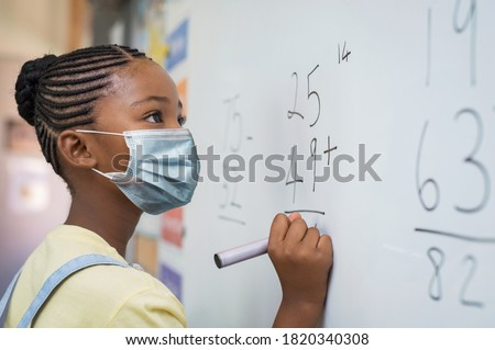 Portrait of african girl wearing face mask and writing solution of sums on white board at school. Black schoolgirl solving addition sum on white board during Covid-19 pandemic. School child thinking. #1820340308