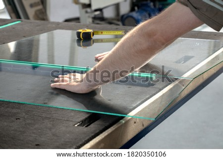 Glazier cuts and breaks glass on a professional table in the workplace Royalty-Free Stock Photo #1820350106