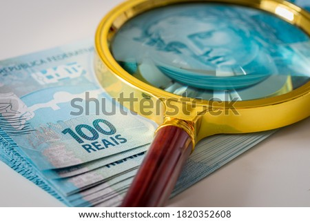 A bundle of Brazilian money with a magnifying glass on it, one hundred Reais banknotes, the highest denomination. Brazil currency fluctuation concept Royalty-Free Stock Photo #1820352608