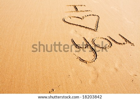 """The words """"I love you"""" written in the beach sand"""