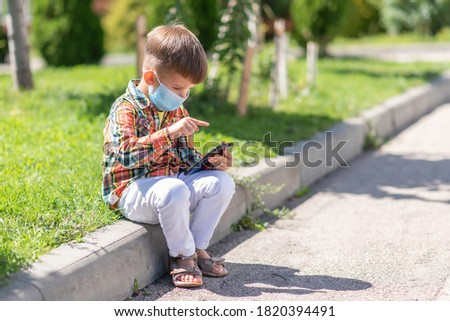 A kid in a medical mask sits on the grass and looks in the phone cartoons in the summer at sunset. Child with a mobile phone in his hands. Prevention against coronavirus Covid-19 during a pandemic