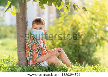 A kid in a medical mask sits on the grass and looks in the phone cartoons in the summer at sunset. Child with a mobile phone in his hand. Prevention against coronavirus Covid-19 during a pandemic