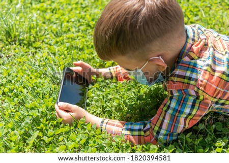 A child in a medical mask lies on the grass and looks in the phone cartoons in the summer at sunset. Kid with a mobile phone in his hands. Prevention against coronavirus Covid-19 during a pandemic