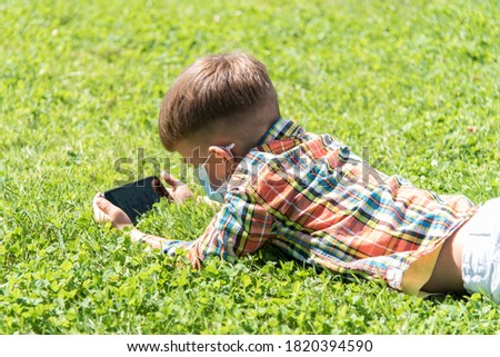 A kid in a medical mask lies on the grass and looks in the phone cartoons in the summer at sunset. Child with a mobile phone in his hands. Prevention against coronavirus Covid-19 during a pandemic