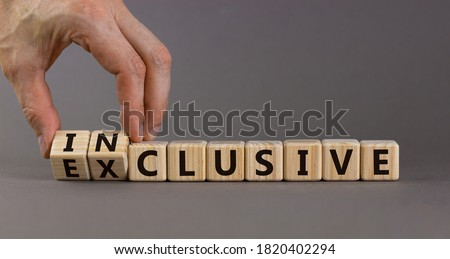 Symbol for a better inclusion. Male hand turns cubes and changes word exclusive to inclusive. Beautiful grey background. Copy space.