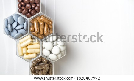 Various capsules and pills with dietary supplements or medicines in hexagonal jars are in the form of a honeycomb Royalty-Free Stock Photo #1820409992
