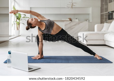 Young attractive woman practicing yoga and stretching body at home using laptop for online class or virtual tutorials. Girl standing in Utthita parsvakonasana exercise, doing Side Angle pose. Wellness Royalty-Free Stock Photo #1820434592
