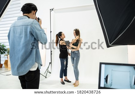 Behind the scene of photo shoot: Asian make-up artist applies makeup on young beautiful model while photographer directions vision creative ideas photoshoot on white background in modern studio.