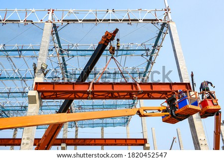 Construction workers installation steel structure girder runway beam lifting by mobile crane and placing on corbel of column concrete at the construction site project #1820452547