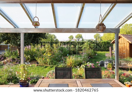 Terrace with glass roofing and a view of the garden Royalty-Free Stock Photo #1820462765