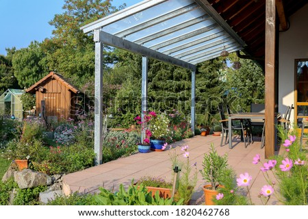 Terrace with glass roofing and a view of the garden Royalty-Free Stock Photo #1820462768