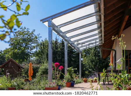Terrace with glass roofing and a view of the garden Royalty-Free Stock Photo #1820462771