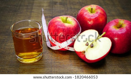 Apple cider vinegar in a glass with apples and a measuring tape on a wooden background. #1820466053