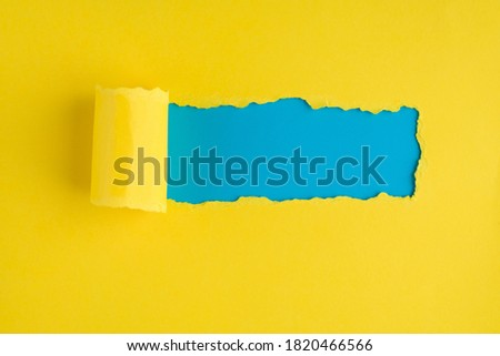 Top above overhead view photo of torn yellow paper over blue background with copyspace