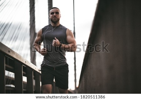 In the photo with a blocked horizon, a muscular guy in light sportswear on an evening run.