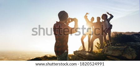 Group of hikers standing on mountain top being photographed by a friend. Man photographing his friends on hiking.