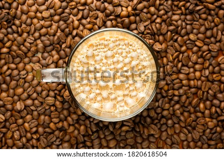 """Flatlay and selective focus picture of foam at """"kopi tarik"""" or pull milk coffee on with coffee bean insight."""