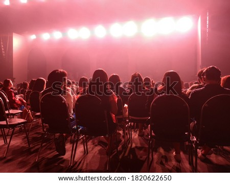 Blurred crowd at social distancing concert venue in Thailand during the coronavirus (covid-19) : Silhouette happy people sitting in front of stage with bright laser light beam.The New Normal #1820622650