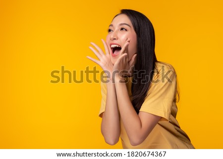 Surprised happy beauty asian woman looking copy space in excitement. Expressive facial expressions. Presenting some product. Beautiful girl act like a telling secret Isolated on yellow background #1820674367