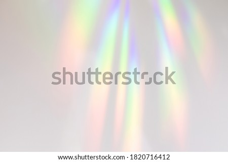 Blurred rainbow light refraction texture overlay effect for photo and mockups. Organic drop diagonal holographic flare on a white wall. Shadows for natural light effects #1820716412