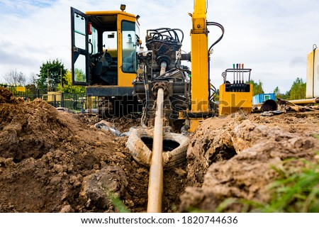 Horizontal directional drilling technology closeup. Drilling machine work process. Trenchless laying of communications, pipes and water pipes Royalty-Free Stock Photo #1820744636