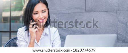 Portrait of asian business woman talking on smartphone using notebook laptop at coffee cafe outdoors. Beautiful girl at desk computer online business. Startup business asia woman, sme marketing banner
