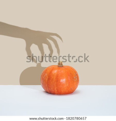 Halloween minimal concept with pumpkin and witch or zombie hand shadow. Creative spooky holiday fun background #1820780657