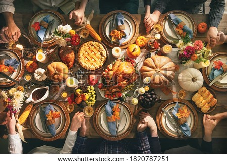 Group of friends or family members giving thanks to God at festive turkey dinner table together. Thanksgiving celebration traditional dinner concept #1820787251