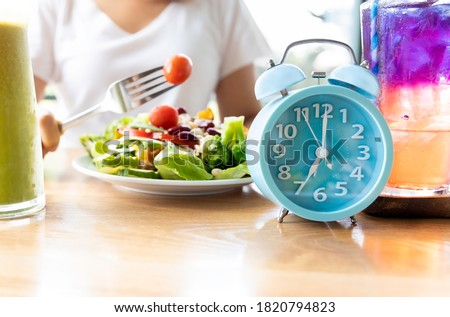 Selective focus of blue clock which woman make a Intermittent fasting with  a Healthy food of salad .Healthy lifestyle Concept. Royalty-Free Stock Photo #1820794823