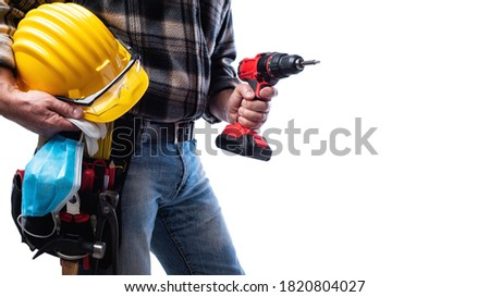 Carpenter isolated on white background, holding a helmet, goggles, leather gloves, surgical mask to prevent infection by the coronavirus and cordless drill. Construction industry work tools. Covid-19.