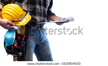 Carpenter isolated on white background, holding a helmet, goggles, leather gloves, surgical mask to prevent infection by the coronavirus and notebook for notes. Construction industry. Covid-19.