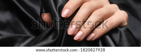 Female hand with pink nail design. Woman hand on black fabric background. Advertising banner ad. Royalty-Free Stock Photo #1820827928