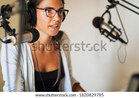 Radio podcast concept - female radio host speaking in microphone in podcasting studio