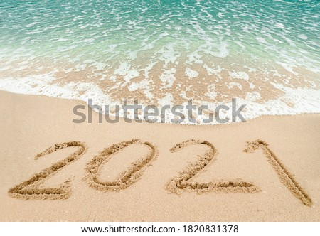 Happy New Year 2021, lettering on the beach with wave and blue sea. Numbers 2021 year on the sea shore, New Years concept. #1820831378