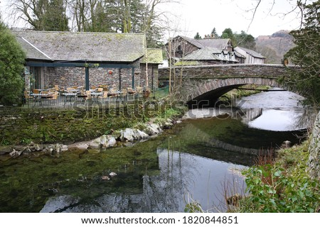 Scenic view of Grasmere village with houses, bridge and ducks floating on the river during early Spring in Ambleside town, Windermere, Lake District National Park, Cumbria, England UK Royalty-Free Stock Photo #1820844851