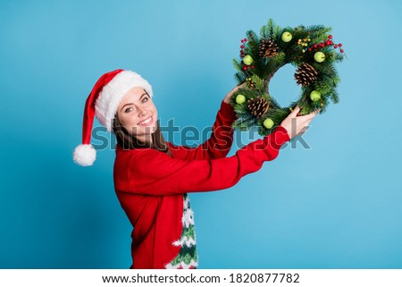 Portrait photo of girl wearing red xmas headwear hanging christmas handmade crafts wreath made of christmas tree branches decorative berries wooden cones isolated on blue color background Royalty-Free Stock Photo #1820877782