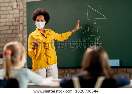 African American elementary school teacher holding mathematics class and wearing protective face mask due to coronavirus pandemic.  Royalty-Free Stock Photo #1820908544